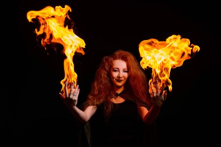 A witch with long curly hair holds a magic fire. Tongues of flame on the palms of a red-haired woman.