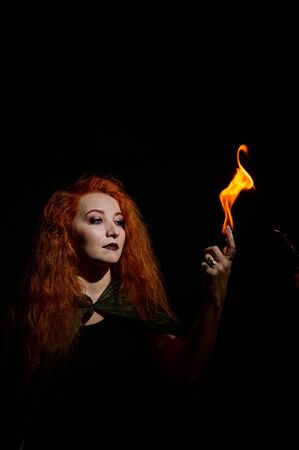 A witch with long curly hair holds a magic fire. Tongues of flame on the palms of a red-haired woman. Flaming eyes. Standard-Bild