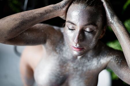 Portrait of a young beautiful woman with very big breasts in silver paint. Naked girl with sparkles of metallic color on the skin. Stockfoto