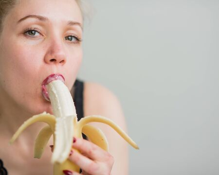 A blonde in black lace lingerie seductively sucks and licks a banana. Woman with sensual red imitates oral pleasure. Banco de Imagens