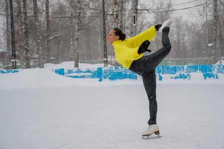 Professional skater on an outdoor ice rink. A woman on knees is preparing a solo program for the competition