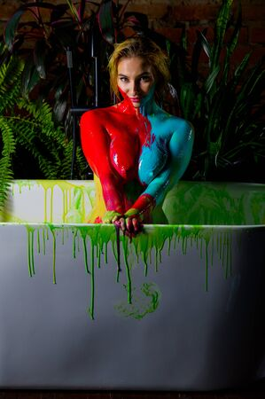 Beautiful woman posing naked in the bathroom against the background of houseplants. On the naked body of a female, streaks of paint flow down. Body painting on a girl body.