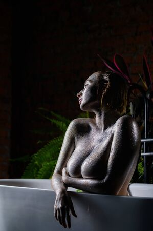 Nude woman with very large with silver bodyart in the bathroom. A girl with an extra large bust with sparkles on her skin takes a shower.