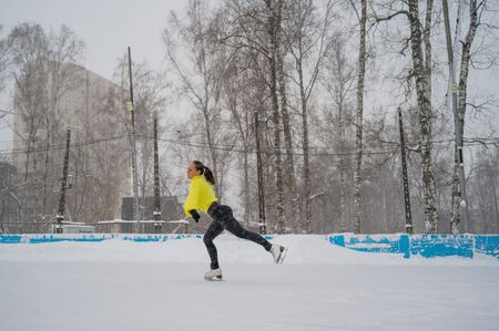 Professional skater on an outdoor ice rink. A woman on knees is preparing a solo program for the competition Banque d'images