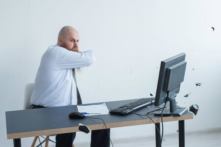 A bearded man is having a nervous breakdown at work. The office manager freaks out and breaks a mug on the monitor. 写真素材