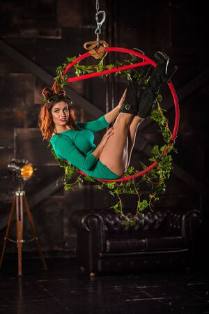 Beautiful woman gymnast performs tricks on an aerial hoop.  Circus acrobat on the ring.