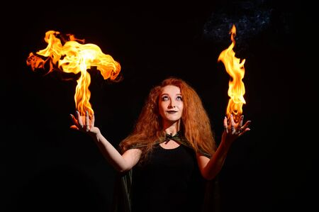 Portrait of a Halloween witch imposes a flame spell. Beautiful redhead woman doing witchcraft holds fire in her hands. Trick or treat.