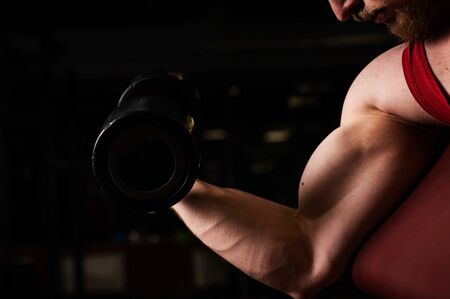 Unrecognizable man doing biceps exercise in the gym. Muscular man is engaged in bodybuilding. Close-up of male hands.