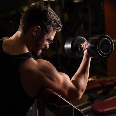 Un hombre guapo con gafas haciendo un ejercicio de bíceps con barra. El chico se dedica al culturismo. Entrenador en el gimnasio con brazos musculosos.