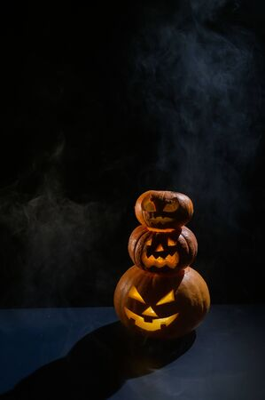Three Halloween pumpkins stand on top of each other in a row. Traditional holiday decoration. Useful as a greeting card. Trick or treat.