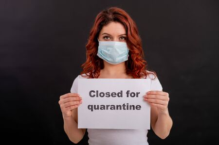Red-haired woman in a medical mask holds a poster. Closed for quarantine. Epidemias of the coronavirus. Fear in the eyes. Imagens