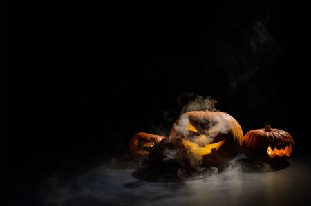 Three halloween pumpkins in the fog. Traditional holiday decoration. Useful as a greeting card. jack-o-lantern is smoking. 写真素材