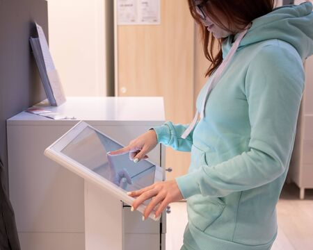 Faceless woman touching the screen of a self-service device in a store. Device store navigator. Self purchase.