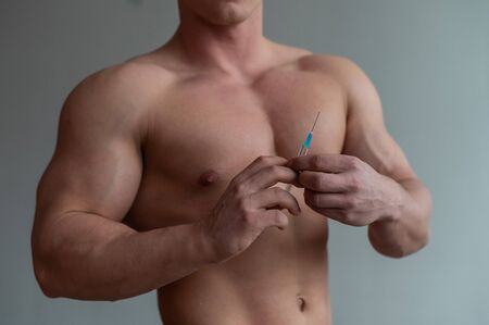 Close-up of a male torso. Unrecognizable shirtless bodybuilder man puts himself an injection of testosterone. Faceless athlete takes dope.