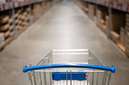 Empty shopping cart in a furniture store warehouse. Supermarket shopping basket aisle with box shelf abstract blur defocused background