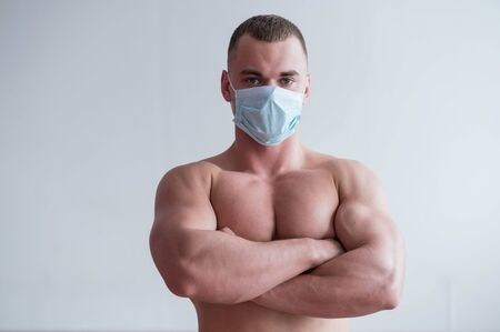 A male bodybuilder in a medical mask crossed his arms over his muscular bare chest. The guy goes in for sports in quarantine. Respiratory protection. Stockfoto