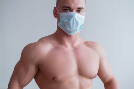 Male bodybuilder in a medical mask with muscular bare chest. The guy goes in for sports in quarantine. Respiratory protection.