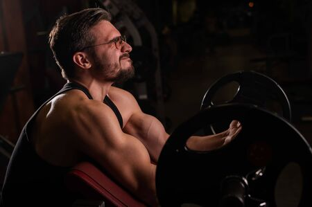 Handsome man with glasses doing biceps exercise with dumbbell. Intelligent Guy is engaged in bodybuilding. Muscular Trainer at the gym.