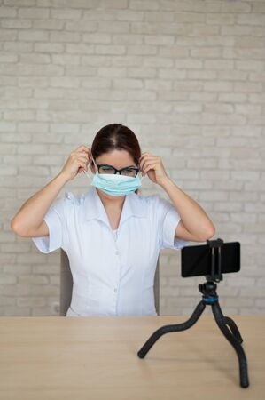 Remote appointment with a physician in quarantine. A doctor shows how to wear a medical mask for protection at an online telephone consultation.