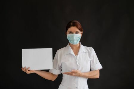 A young doctor in a medical mask holds a white poster on a black background. Female nurse in uniform pointing to a blank billboard.