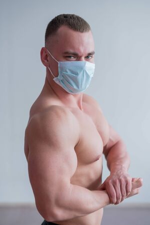 Bodybuilder with a naked torso in a medical mask. Muscled with a guy doing sports in quarantine. Respiratory protection.