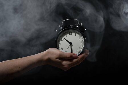 A woman holds an alarm clock in a studio full of smoke. White fog enveloped a round retro mechanical watch. Standard-Bild - 143946604