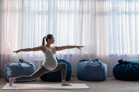 Pregnant woman practice yoga. A girl in the third trimester leads Pilates. Classes to prepare for childbirth. Waiting for the baby. Warrior Pose.