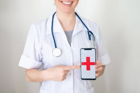 Unrecognizable female doctor holds a smartphone with a red cross on the screen. The nurse smiles and points to the screen of a cell phone. Banque d'images - 144166941