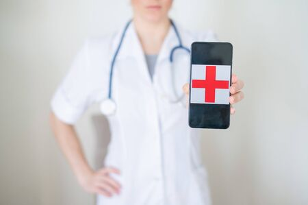Faceless female doctor holds a smartphone with a red cross on the screen. unrecognizable nurse in medical coat demonstrating cell phone Banque d'images - 144175162