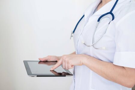 Unrecognizable female doctor in uniform uses a tablet computer. A medical worker contacts patients on a device. Cropped Banque d'images - 144175305