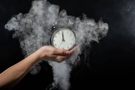 Close-up of a female hand holding a clock on a black background in smoke. Alarm clock at midnight in a mystical fog 写真素材