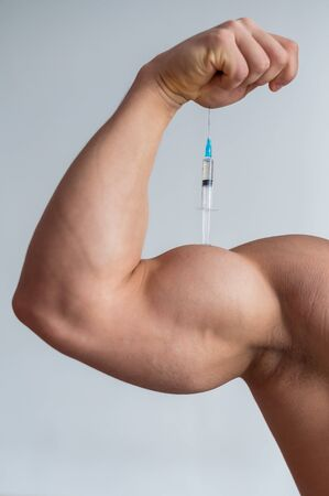 Close-up of male biceps. Unrecognizable male bodybuilder puts himself an injection of testosterone. Faceless athlete takes growth hormone. Vertical