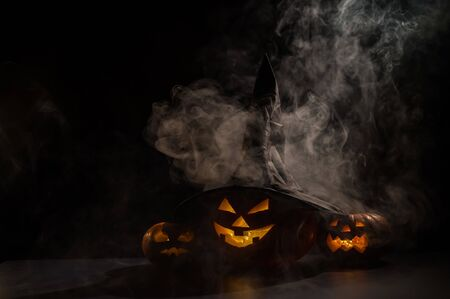 Three creepy Halloween grinning pumpkins glow in the dark among the fog. jack-o-lantern in a witch hat on a black background in smoke