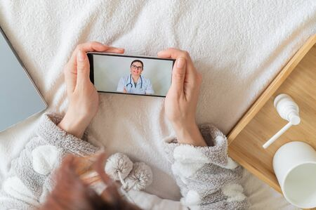 A faceless woman is at home in bed and consults with a healer using a webcam. The doctor remotely consults the patient on a video call.