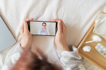 Unrecognizable woman with a cold talking to a doctor through video chat on a smartphone. friendly doctor gives an online consultation to the patient.