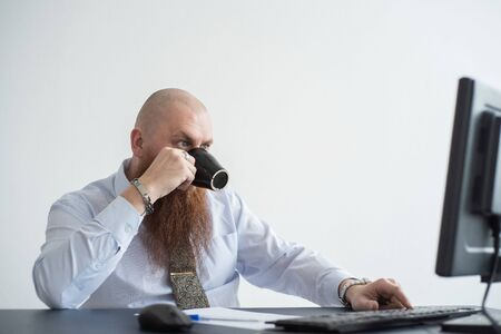 Focused bald man with a red beard drinks coffee and works at the computer. Male manager in a white shirt at a personal computer in the office.