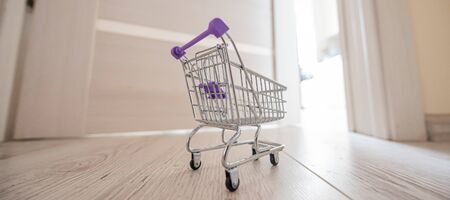 Grocery cart at the open door. Delivery of products. Mini trolley for contactless delivery. Banco de Imagens