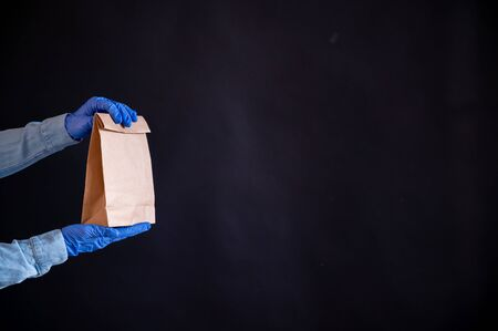 Female hands in a blue glove holds a brown paper bag on a black background. Safe food delivery to your home. A courier in a denim shirt holds out a craft cardboard bag to a customer.
