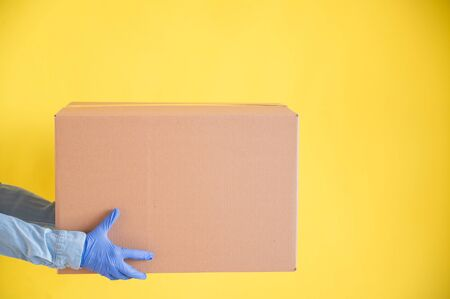 Close-up female hands in gloves holds a small cardboard box on a yellow background. Online store with home delivery. A courier in a denim shirt holds out a craft cardboard bag to a customer.
