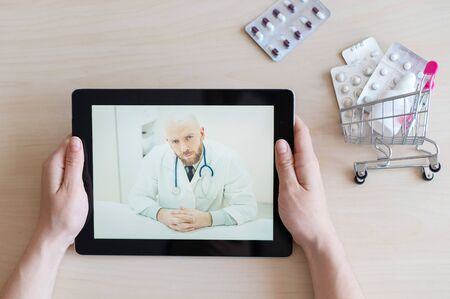 The patient communicates with a male therapist via video chat on a digital tablet. Woman at online consultation with a doctor. Online pharmacy concept. Mini medicine trolley.