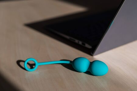 Blue silicone vaginal kegel balls on a table next to a laptop. Sex toy for building is synchronized with a computer. Intimate muscle trainer for women health. Stockfoto - 146952953