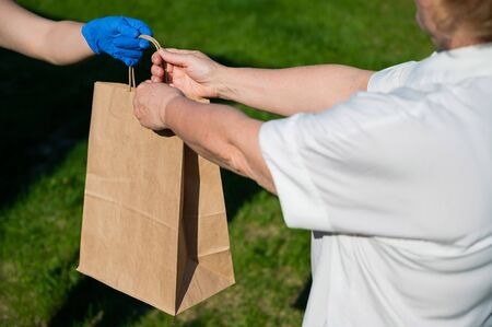 Female courier in gloves bringing food package to retired old woman. Woman handing a paper bag with groceries to a female pensioner outdoor. Delivery service during quarantine. Close-up. Zdjęcie Seryjne