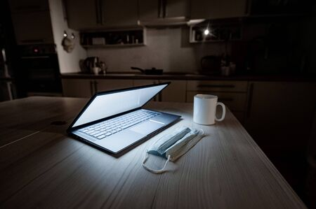 Remote work overtime during the quarantine period in the home office. Working atmosphere in the kitchen on a laptop in the dark late at night. Coffee mug and medical mask on the table