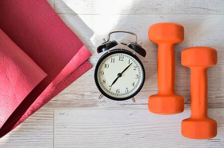 Top view on orange dumbbell alarm clock and raspberry yoga mat. The concept of home sports during quarantine. Fitness time. Early rise for classes Zdjęcie Seryjne