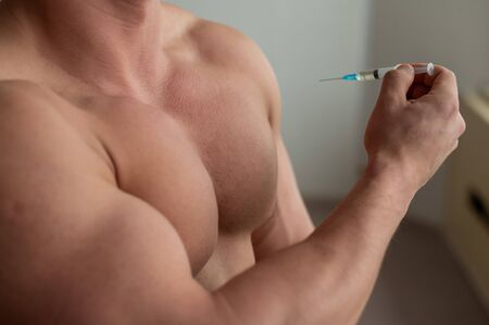 Close-up of a naked male torso. Unrecognizable shirtless bodybuilder man puts himself an injection of testosterone. Faceless athlete takes dope.