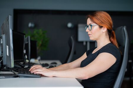 Redhead woman in glasses and casual wear working overtime. Focused girl alone works on a computer in an empty office. Deadline. The IT specialist enthusiastically works on the weekend. Banco de Imagens