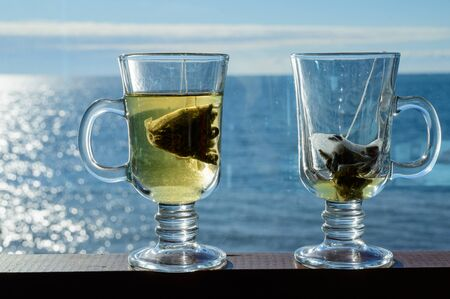 Two transparent glass cups with a bag of green leaf tea on a background of the sea.