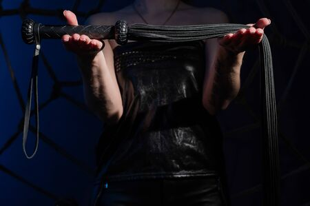 Black leather lash in the hands of an unrecognizable woman. Cropped photo of bdsms toys. Punishment and pleasure. A woman stands in the dark and holds a whip in her palms.