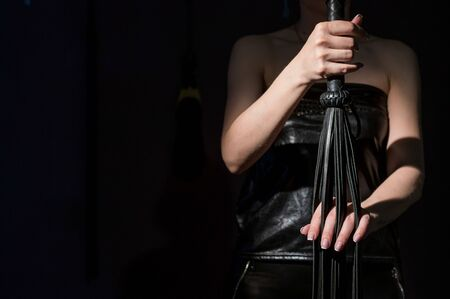 BDSM concept. A woman in a leather corset holds a black lash with a long fringe. Role-playing games for adults. Close-up of sex toys for domination. The whip in female hands.
