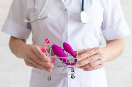 The faceless gynecologist recommends buying a clitoral vaginal vibrator to maintain womens health. The doctor holds a mini trolley and a masturbator for vivid orgasms.
